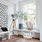 vintage white interior with black white wallpaper with tripod floor lamp and white chair and white console and potted plant and glass window and wooden floor