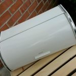 white-Brabantia-Bread-Box-with-Metal-Chrome-and-Vintage-style-with-17.5-x-10-inch-and-Roll-Top-model-near-the-brick-and-put-on-wooden-box