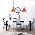 white-Eames-molded-plastic-chairs-with-black-and-white-dining-table-and-orange-pendant-lamp-in-white-walls-and-brown-floor-also-a-white-brown-wall-clock