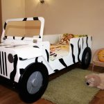 white-buggy-bed-car-design-for-kids-and-pillow-with-monkey-picture-and-a-doll-on-the-green-carpet-on-the-wooden-floor