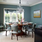 white-chandeliers-over-wooden-dining-table-with-soft-navy-blue-chairs-near-black-cabinets-and-white-windows
