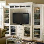 white entertainment system furniture with glass doors and 3 drawers decorated in living room with striped rug on black rug plus beige cozy sofa