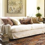 white slipcover for sofa a lot of decorative pillows in different pillowcases a pile of books global rug idea