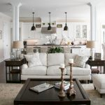 white-sofas-with-low-arm-and-white-pillows-and-carpet-on-the-wooden-floor-and-dark-brown-coffee-table-with-candles-centerpiece-and-photos-and-brown-table-with-pendant-lamps-over-kitchen-island
