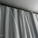 white stripped blue color of shower curtain lliners with black rod near light blue wall