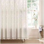 white-victorian-lace-shower-curtains-near-white-windows-and-flowers-in-white-vase-and-white-bathtub