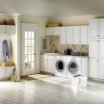 Wide And White Laundry Room Idea With White Washed Flooring And Cabinetry And Glass Door And Basket Shelves