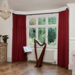 wonderful window treatment with curtain rods for bay windows and also red curtain together with impressive wooden floor and antique sideboard plus crystal ceiling lamp