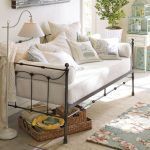 Black metal pottery barn daybed with white mattress and white pillows some rattan boxes as storage small sized rug with flower motif