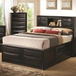 Black painted wooden bed frame with storage underneath and shelf plus a pair of cabinets in headboard