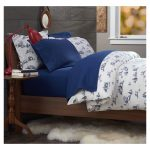 Blue And White Winter Duvet Cover On Mattress And Pillows Near Red Table Lamp On Woodern Small Side Table ANd Fur Rug