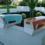 Blue and orange modern boxes for mails laid on giant white box planter