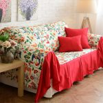 Colorful floral themed slipcover for sectional sofa with two throw pillows