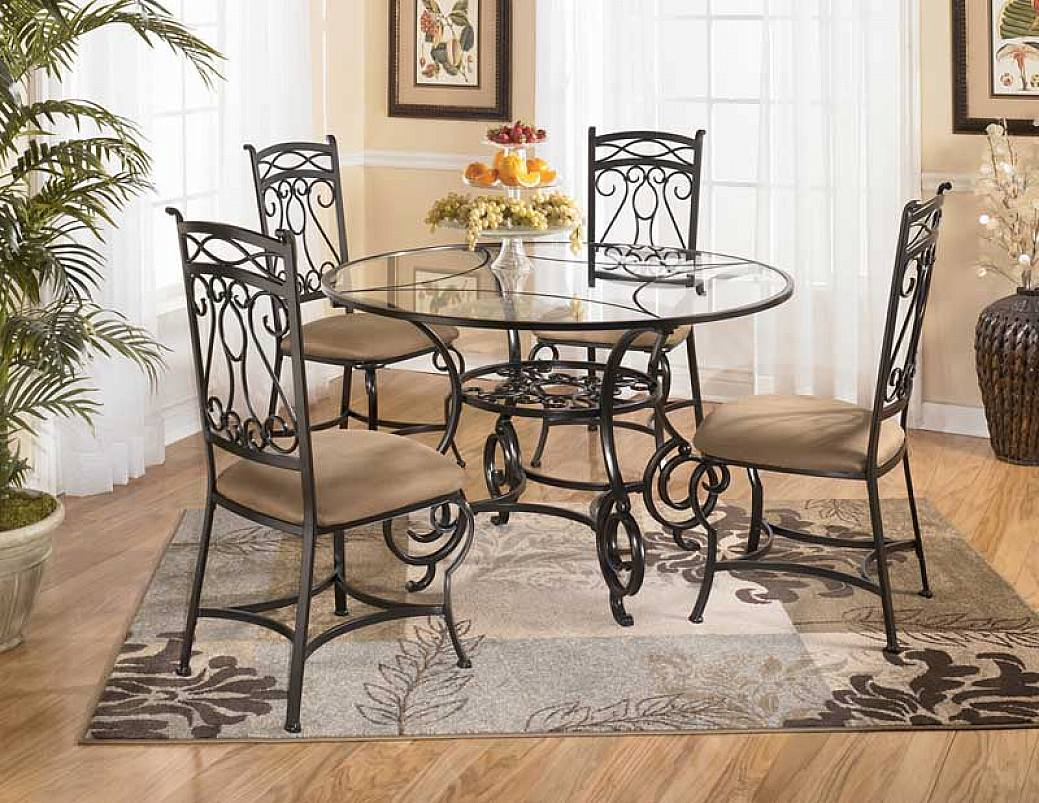 Glass Round Wrought Iron Kitchen Table With Brown Chairs And Decorative Rug  In Warm Room