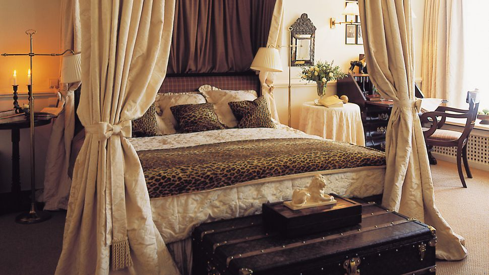Excellent and real safari bedroom decor idea  King sized bed frame with  headboard and leopard skin print bed linen and pillows light beige
