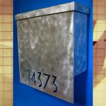Metal modern mailbox with blue background