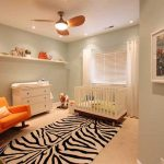 Modern baby bedroom design in white theme with zebra colored bedroom rug idea bright orange sofa for nurturing  a unit of white storage and white floating shelf a ceiling fan with lamp white crib
