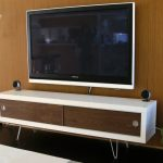 Modern media cabinet by IKEA with white frame and wooden door pin hair legs a flat TV set