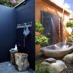 Modern outdoor shower design with wall mount showerhead a bathtub made from natural stone white wall hookers for hanging clothes or towel tree trunk side table and tree trunk bench