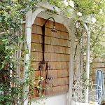 Outdoor Shower Idea In Tropical Garden Theme With Wall Mounted Showerhead White Painted Wood Gate With Full Of Green Plants