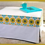 Oversized white slipcover for ottoman with beautiful flower patterns a blue covered book and blue cup for tea or coffee