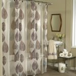 Semi transaparent cloth shower curtain with leaves pattern small bathroom sink with metal base a decorative mirror with wood frame small side table with metal legs