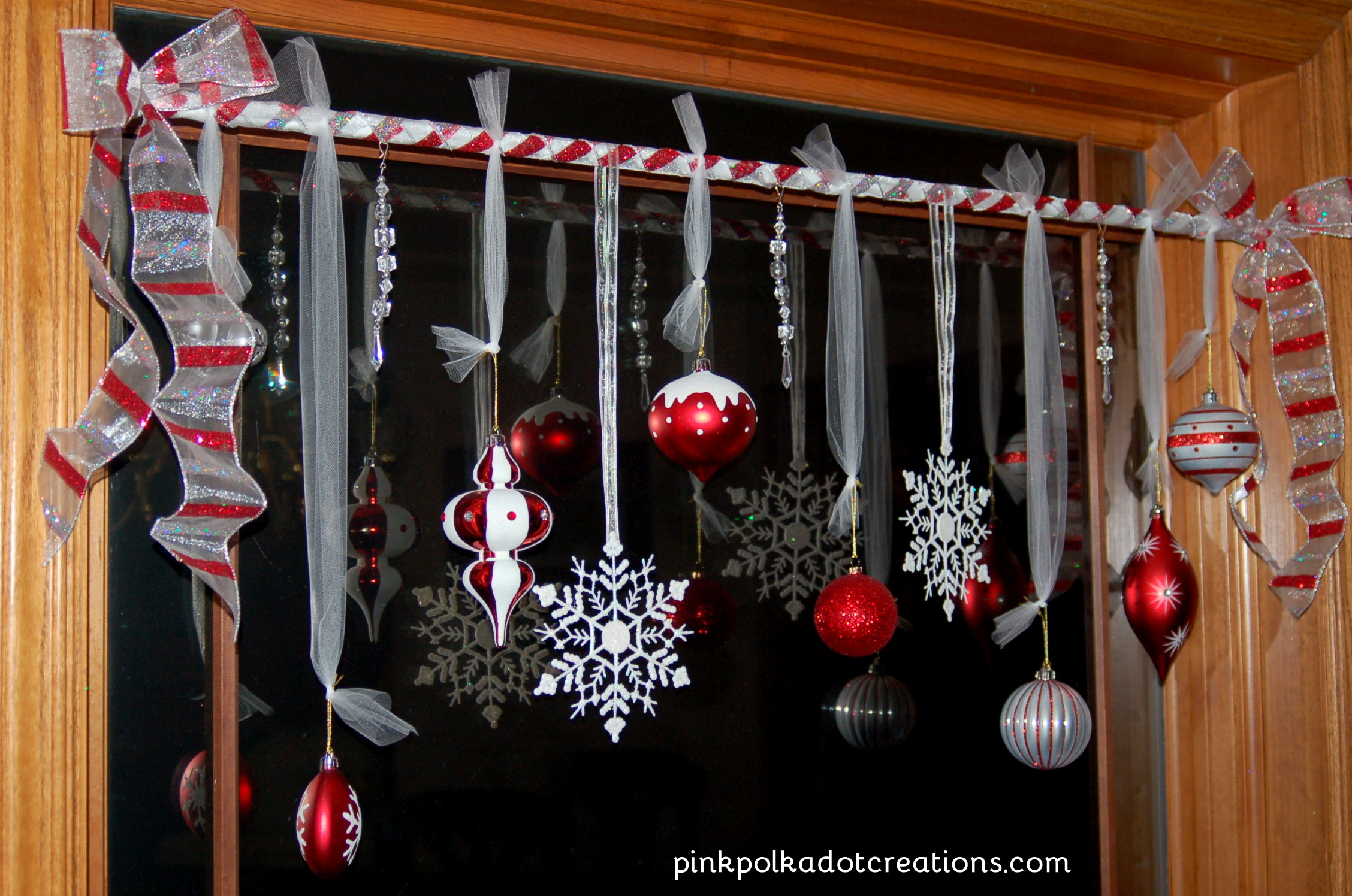silver and red ribbon with ornaments for christmas on window with wooden frame - How To Decorate Windows For Christmas