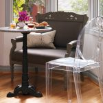 Smaller Round White Marble Top Bistro Table With Classic Black Wooden Base Transparent Plastic Chair An Armchair With White Throw Pillow