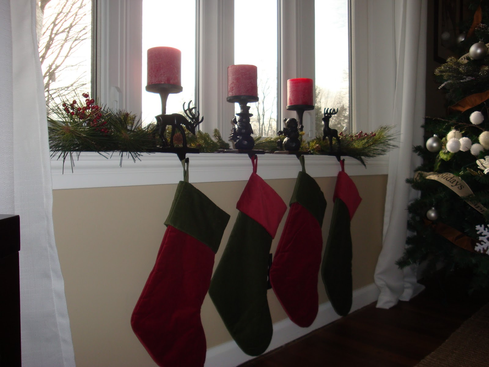 socks plants and red candle christmas decoration on window near christmas tree