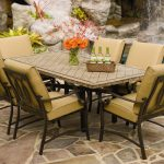 Stone Patio Table With Rectangular Big White Size And Light Color Chairs Near Pool With Waterfall