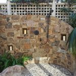 Transition Outdoor Shower Idea Which Presents Rustic And Modern Style In One Look Black Handheld Showerhead Three Wall Niche For Putting Candle Holders Small Natural Stones For Shower Floor System