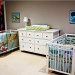 Two units of baby cribs in white which are completed with cozy mattresss a storage system in white