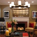 White And Stone Design Of Fireplace In Classic Living Room With Candles Chandelier And Yellow Chairs Double Lamps