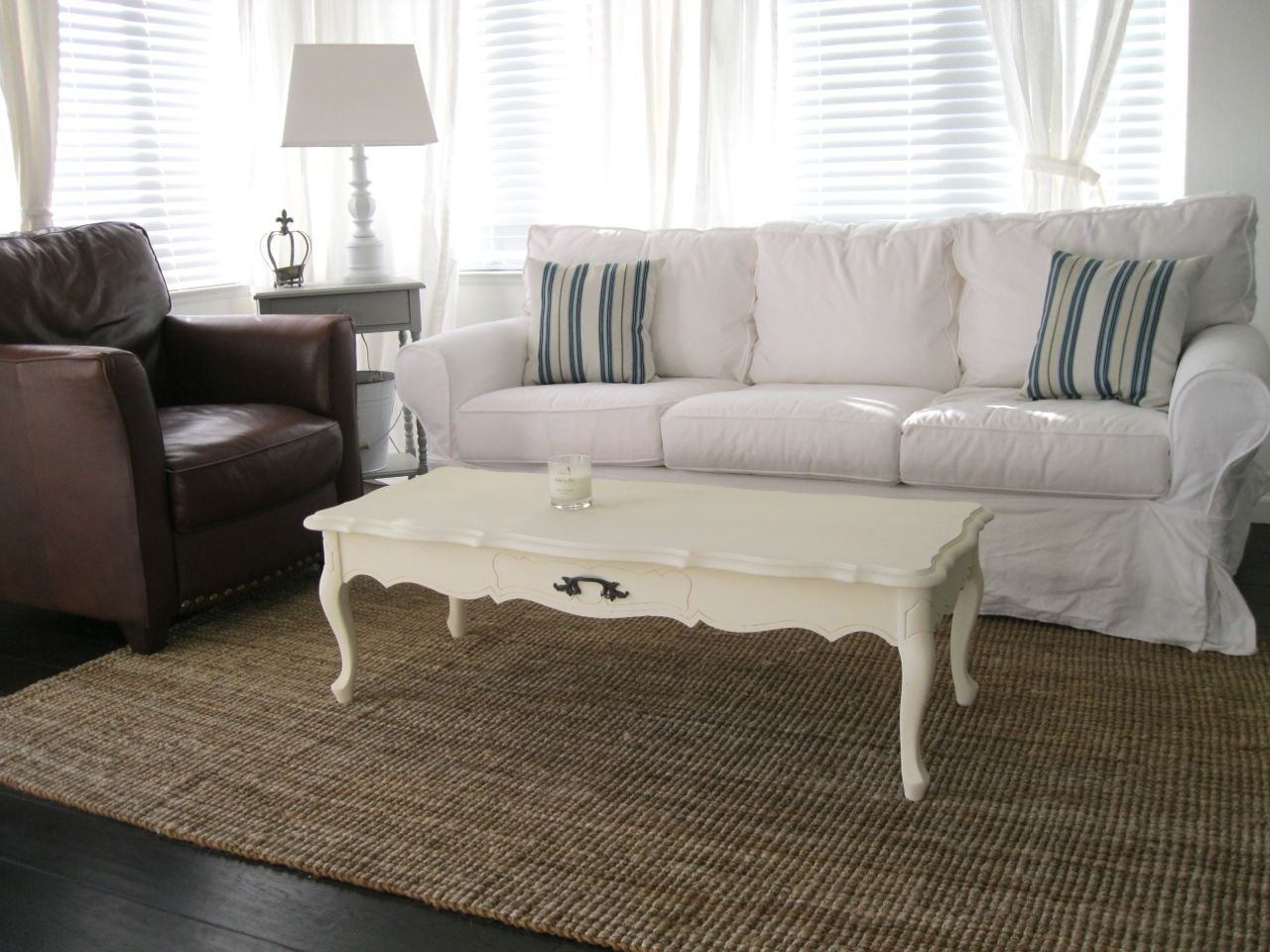 White Slipcovered Sofa With Long Table And Rug