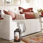 White comfy pottery barn daybed with red dominant accent pillows round side tables with metal base  white jute rug and a permadani