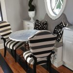 White marble bistro table in round shape a couple chairs with strip pattern white bench with backrest and monochromotic pillows a pair of white painted wooden storage units