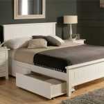 Wooden White Bed With Drawers Underneath And Small Cabinet With Standing Lamp Grey Fur Rug