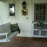 adorable and elegant gray porch swing set with chain and brick paved flooring and white vinyl siding and glass door and window and lantern