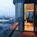 adorable balcony of apartment with city view with glass railing design and wooden floorand gray facade