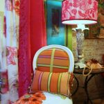 adorable bohemian room idea with metal black scrolled table and pink custom lamp shade and white orange chair and colorful curtain with brick wall