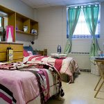 adorable college dorm room idea for two persons with wooden wall storage and vanity and desk and glass window and closet and white flooring