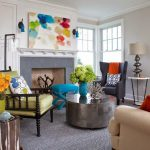 adorable colorful painting for interior design above fireplace with yellow gray and creamy sofa with metallic coffee table and gray area rug