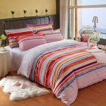 adorable contemporary bedroom design with stripe patterned sheet with colorful accent and wooden floor and round end table and white ikea sheepskin rug