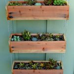 adorable hanging succulent planter idea on green wooden board siding and box wood with shrub and hydrangea