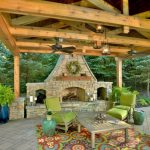 adorable outdoor patio with paved floor and wooden pergola and stone fireplace and green chairs and rustic coffee table and patterned area rug