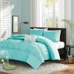 adorable sweet turquoise bedding sheet and pillows and black platform bed and gray area rug and wooden floor and glass window and sheer white curtain