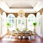 adorable white sunroom design idea with arched window style and vault ceiling idea and dining table with indoor plan and wooden floor