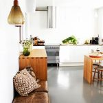 adorable white vintage kitchen design with white cabinetry and wooden island and dining table and brown leather bench sofa for seating with cushions