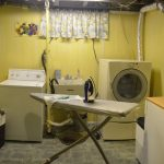 adorable yellow basement laundry design with ironing board and wooden storage and sleeve for window and patterned flooring
