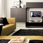 adorablemodern living room design with floating gray cabinet and tv console and yellow couch idea with round black coffee table and black rug